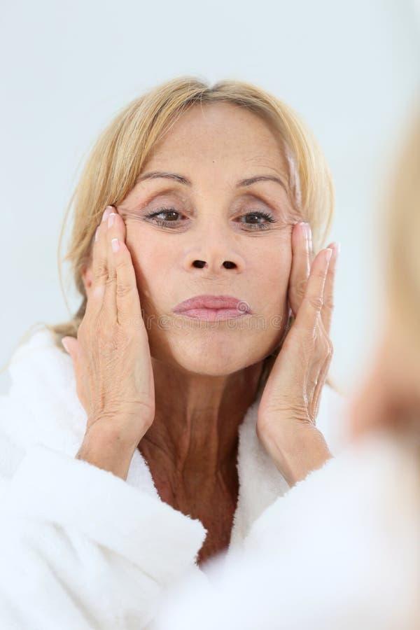 Ältere Frau, die Gesichtscreme aufträgt stockfotografie