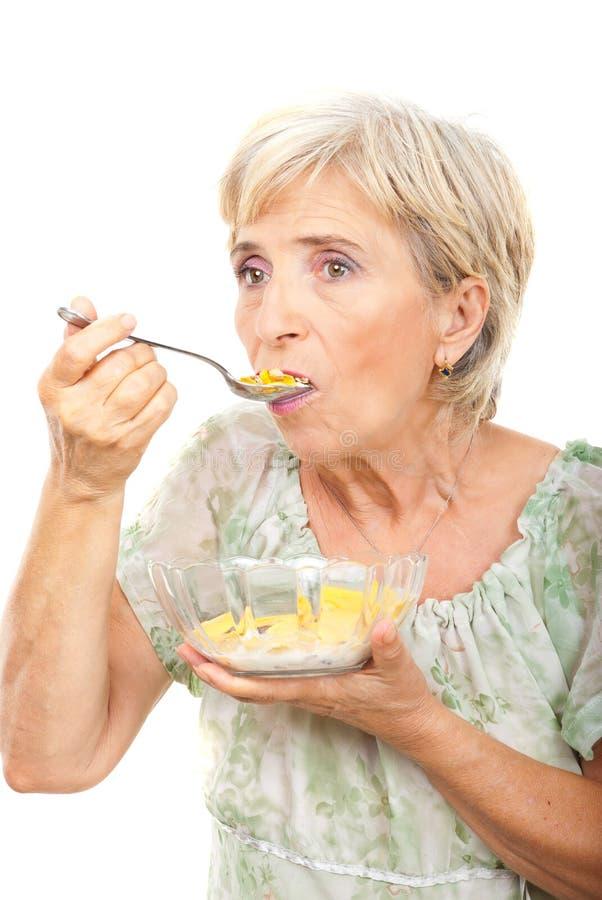 Ältere Frau, die Getreide isst lizenzfreies stockfoto