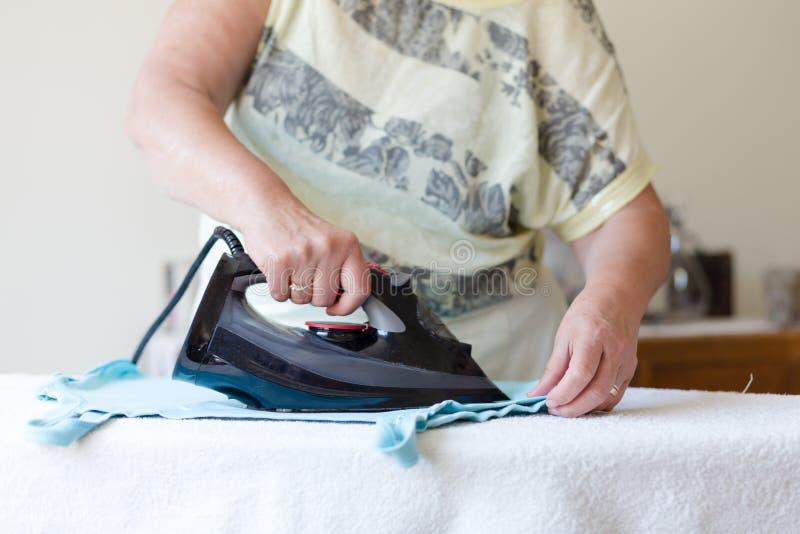 Ältere Frau, die gewaschene Stoffe im hellen Raum bügelt stockfotografie