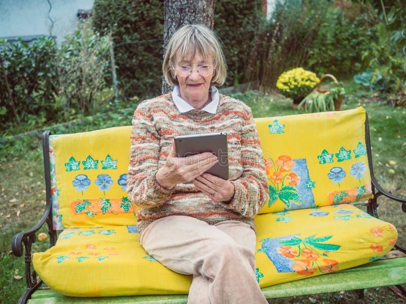 Ältere Frau, die glücklich das Netz auf Tablette surft stockfotos