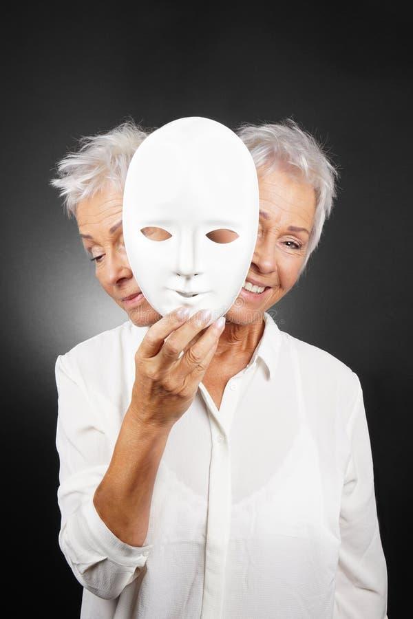 Ältere Frau, die glückliches und trauriges Gesicht hinter Maske versteckt lizenzfreies stockfoto