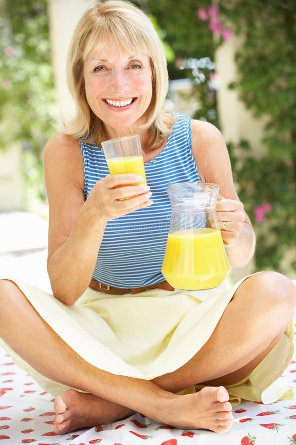 Ältere Frau, die Glas Orangensaft genießt lizenzfreie stockfotografie