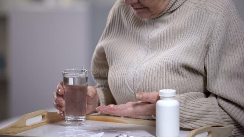 ?ltere Frau, die Glas Wasser h?lt und Pillen in Gesundheitszentrum, Gesundheit nimmt lizenzfreies stockfoto