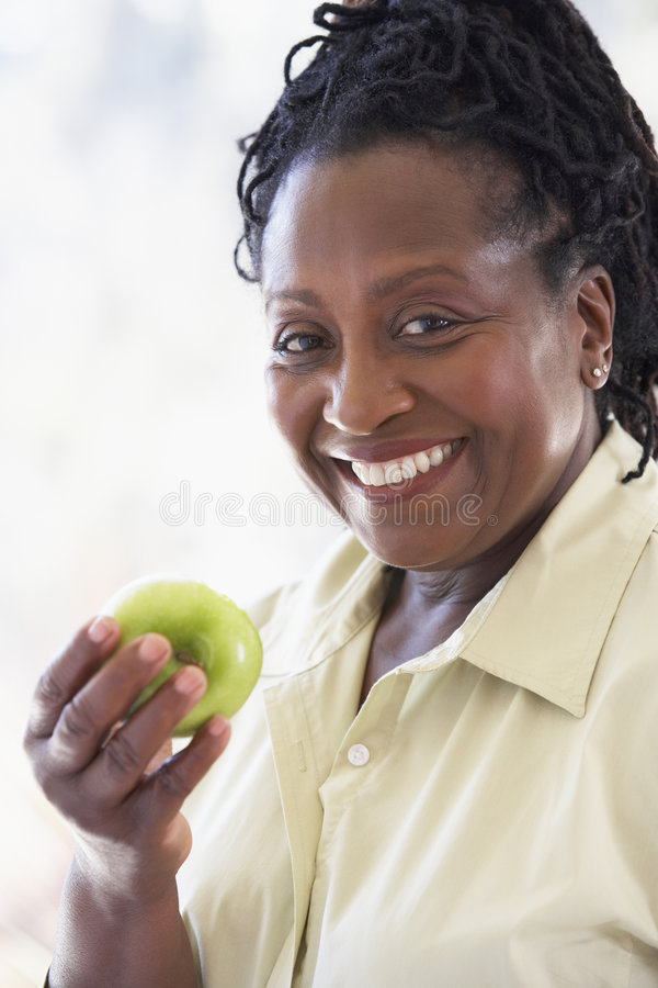 Ältere Frau, die grünen Apple isst stockfoto