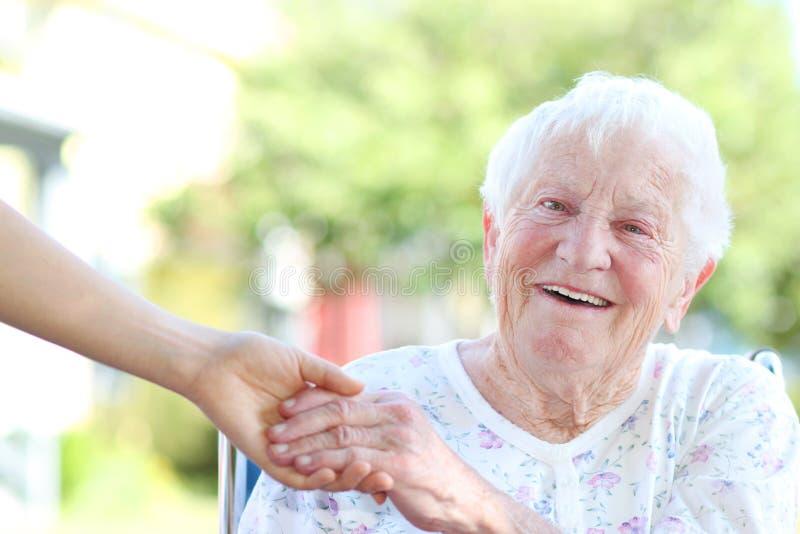 Ältere Frau, die Hände mit Wärter anhält stockfotos