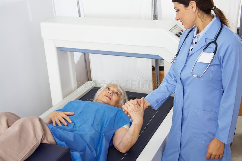 Ältere Frau, die Hand von Doktor in der Radiologie hält lizenzfreie stockfotografie