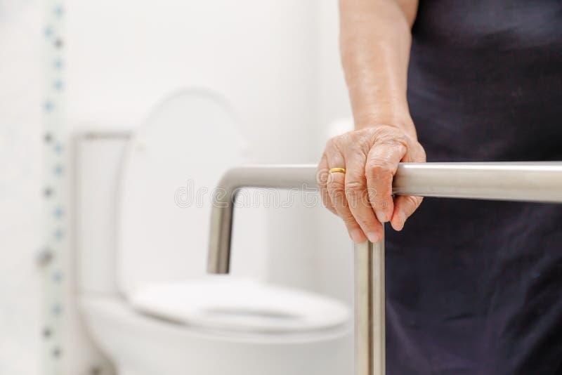 Ältere Frau, die an Handlauf in der Toilette hält stockfotos