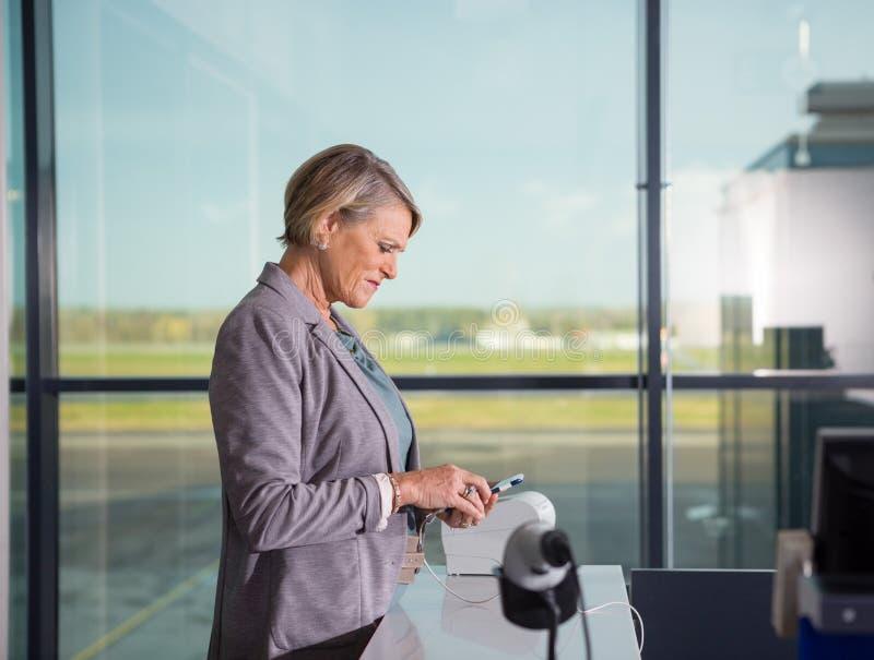 Ältere Frau, die Handy im Flughafen verwendet stockbild