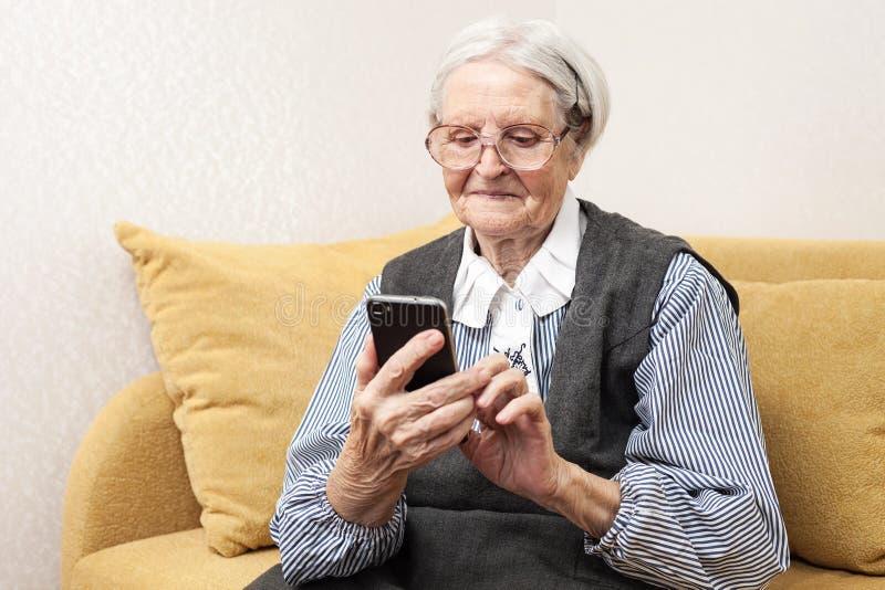 Ältere Frau, die Handy verwendet stockfoto