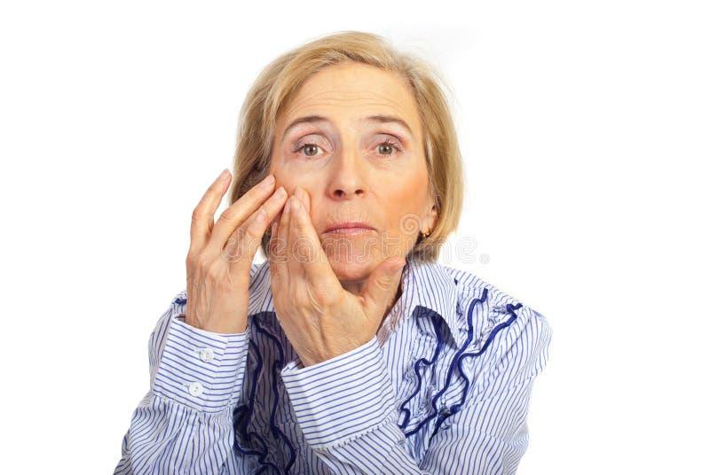 Ältere Frau, die Hautgesicht überprüft stockbilder