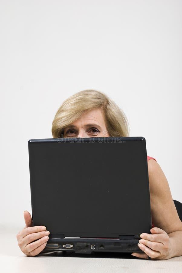 Ältere Frau, die hinter Laptop sich versteckt