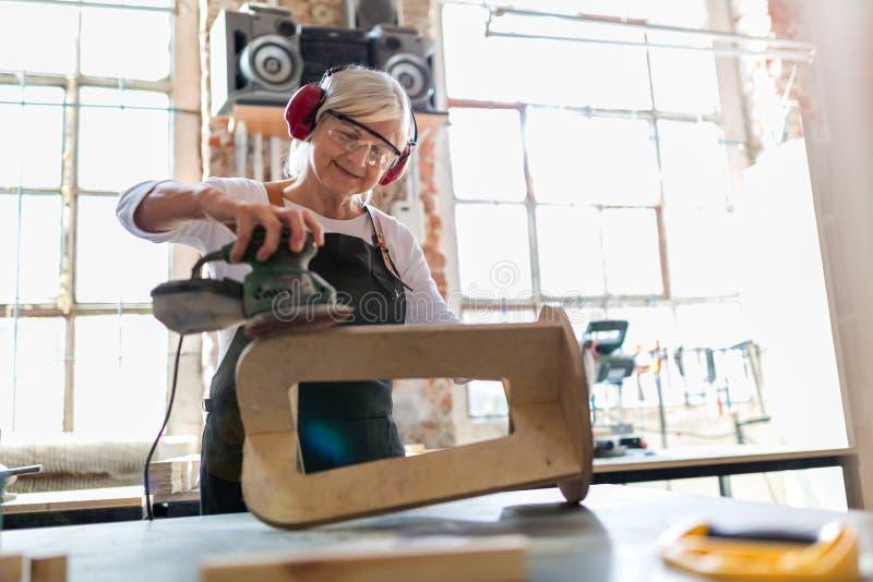 Ältere Frau, die Holzarbeit in einer Werkstatt tut lizenzfreie stockfotos