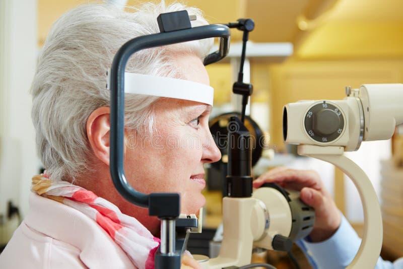Ältere Frau, die Hornhaut überprüft erhält stockfotografie