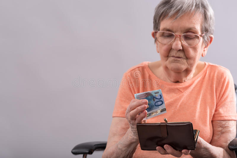 Ältere Frau, die ihr Geld zählt stockfotografie