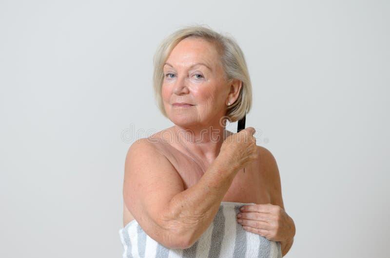 Ältere Frau, die ihr Haar kämmt lizenzfreie stockfotos