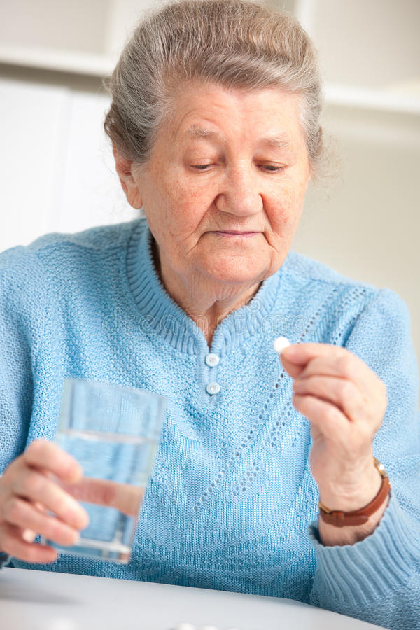 Ältere Frau, die ihr Medizin einnimmt stockbilder
