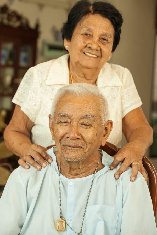 Ältere Frau, die ihrem Ehemann eine Massage gibt stockfoto