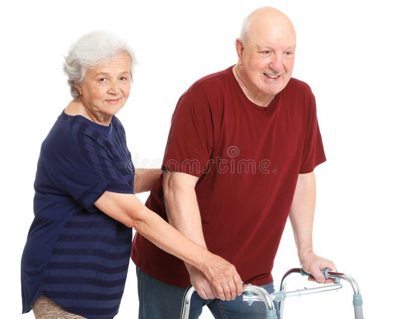 Ältere Frau, die ihrem Ehemann mit gehendem Rahmen hilft stockfoto