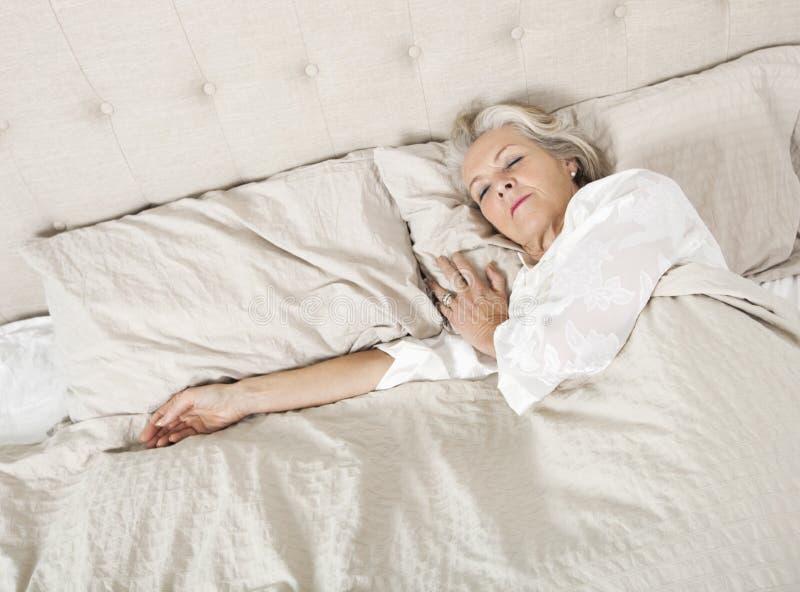 Ältere Frau, die im Bett schläft stockfotos