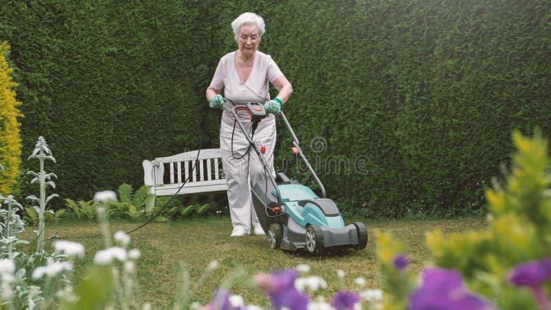 Ältere Frau, die im Garten mit Mäher arbeitet lizenzfreie stockfotografie