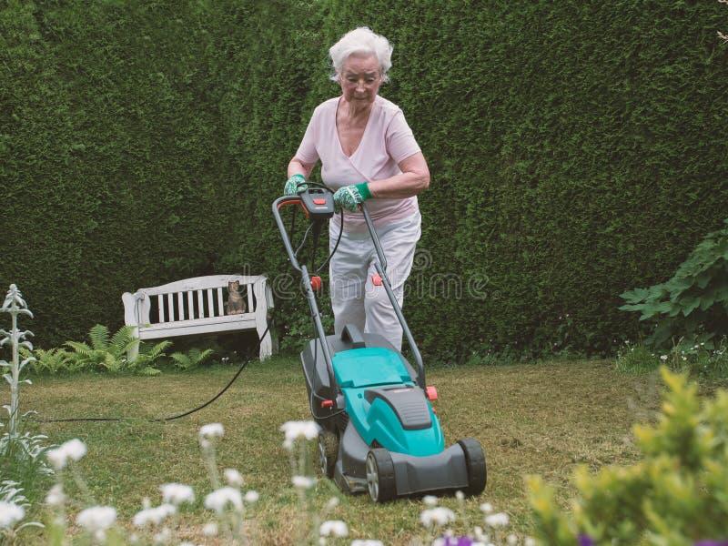 Ältere Frau, die im Garten mit Mäher arbeitet stockbild