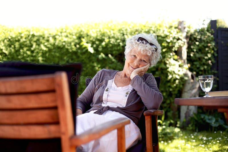 Ältere Frau, die im Hinterhofgarten sich entspannt lizenzfreie stockfotografie