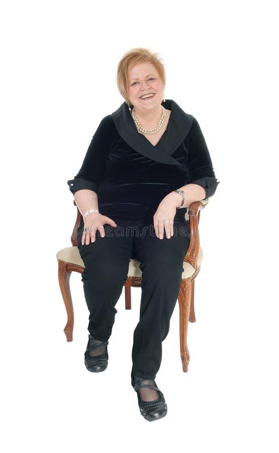 Ältere Frau, die im Lehnsessel sich entspannt lizenzfreies stockbild