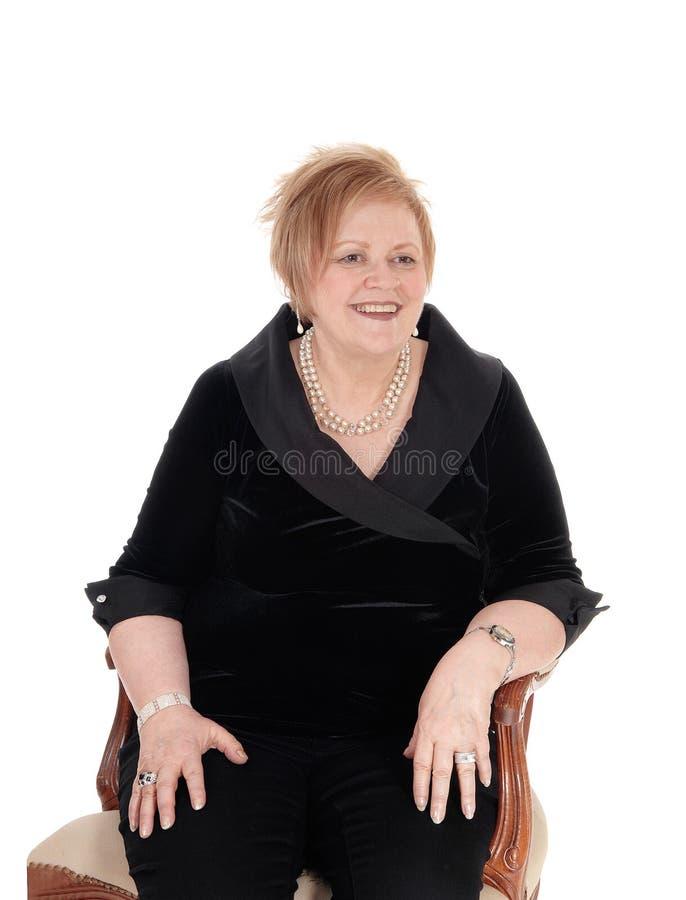 Ältere Frau, die im Lehnsessel sich entspannt lizenzfreies stockfoto