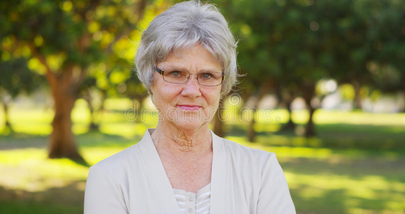 Ältere Frau, die im Park betrachtet Kamera steht lizenzfreie stockfotos
