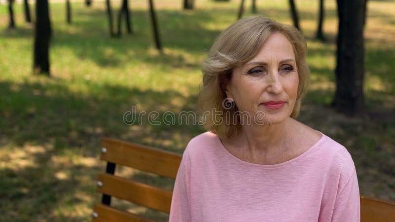 Ältere Frau, die im Park, Ruhestandsfreizeit, Wartegenießend mann sitzt lizenzfreie stockfotografie
