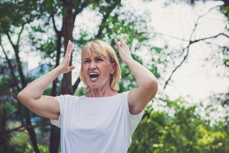 Ältere Frau, die im Park schreit stockbilder