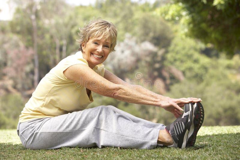 Ältere Frau, die im Park trainiert stockfoto