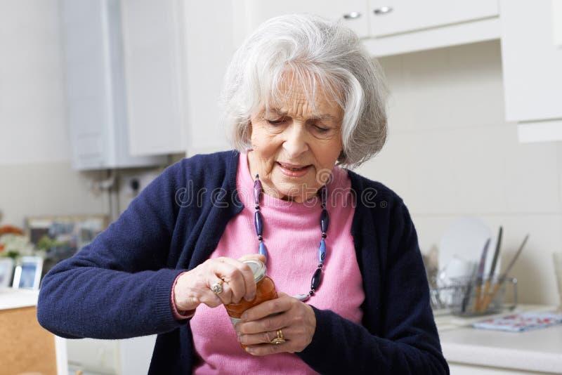 Ältere Frau, die kämpft, um Deckel Glas zu entfernen lizenzfreie stockfotos