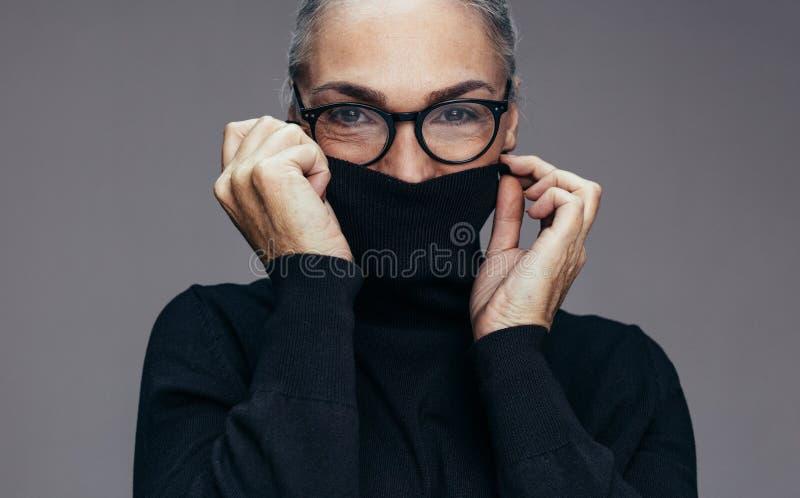Ältere Frau, die kalt sich fühlt stockfotografie
