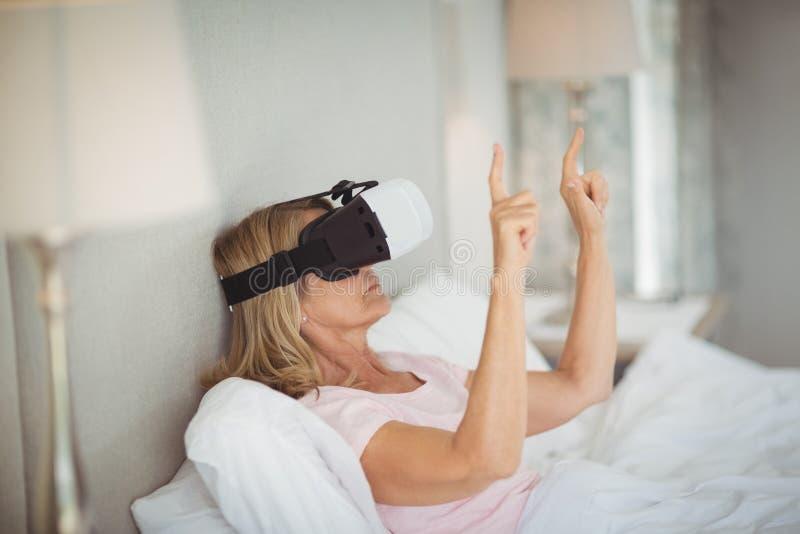 Ältere Frau, die Kopfhörer der virtuellen Realität verwendet stockfoto
