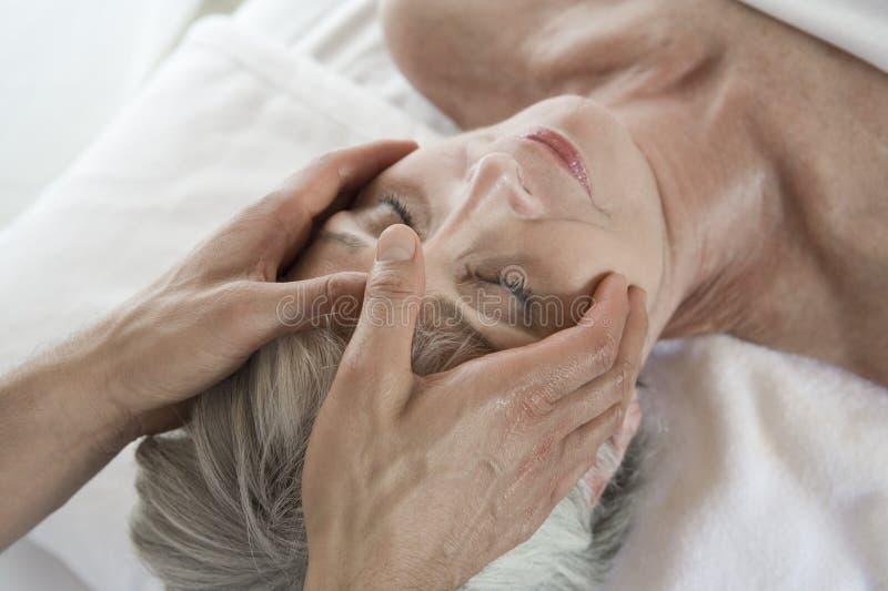 Ältere Frau, die Kopfmassage am Badekurort empfängt lizenzfreie stockbilder