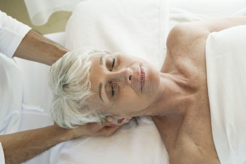 Ältere Frau, die Kopfmassage empfängt lizenzfreie stockbilder