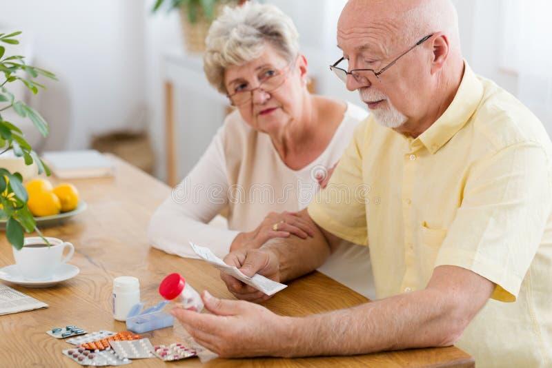 Ältere Frau, die kranke Broschüre des älteren Mannes Leseder Droge stützt stockfoto