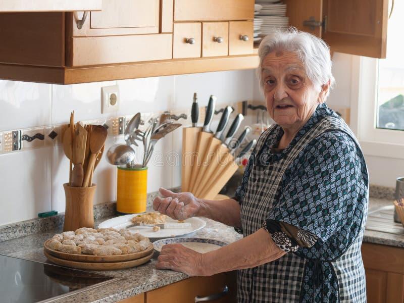 Ältere Frau, die Kroketten zubereitet stockbilder