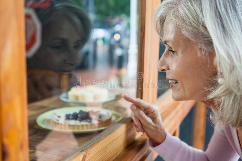 Ältere Frau, die Lebensmittel durch Glasfenster betrachtet lizenzfreies stockfoto