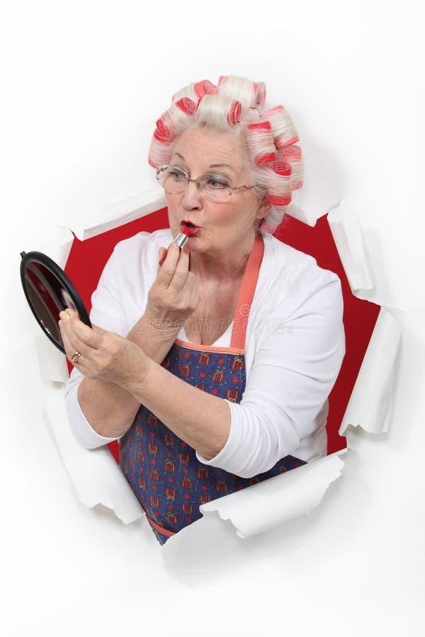 Ältere Frau, die Lippenstift anwendet lizenzfreie stockfotos