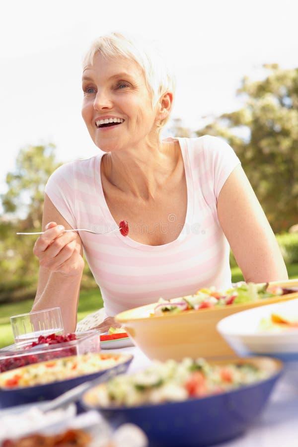 Ältere Frau, die Mahlzeit im Garten genießt stockfotografie