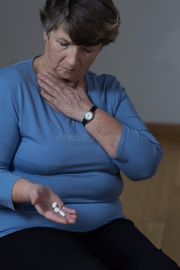 Ältere Frau, die Medizin einnimmt stockfotos