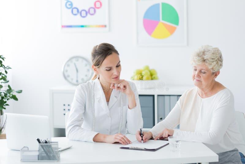 Ältere Frau, die medizinische Informationen füllt lizenzfreie stockfotografie