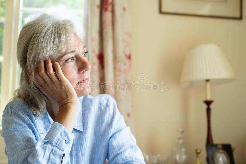 ?ltere Frau, die mit der Krise zu Hause schaut aus Fenster heraus leidet stockbild