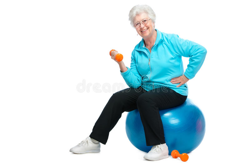 Ältere Frau, die mit Gewichten in der Gymnastik arbeitet stockfotografie