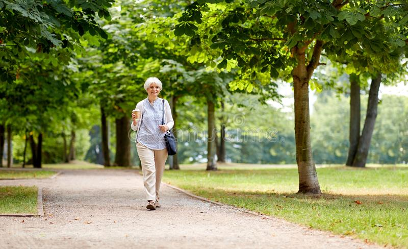 Ältere Frau, die mit Mitnehmerkaffee am Park geht stockfoto