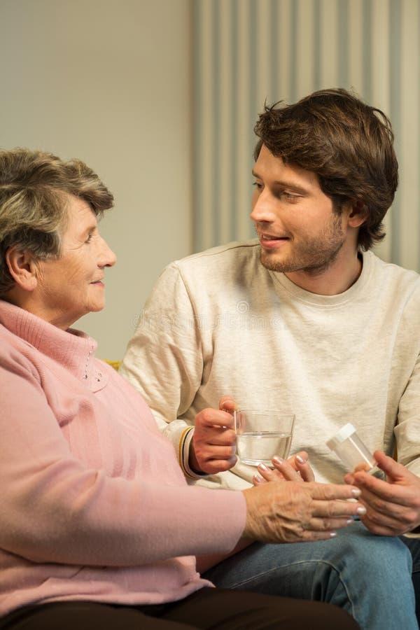Ältere Frau, die mit Pflegekraft spricht stockbilder
