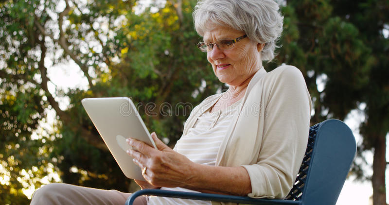 Ältere Frau, die mit Tablette am Park sitzt lizenzfreies stockbild