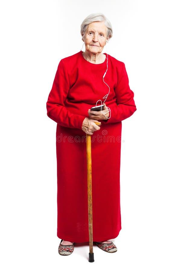 Ältere Frau, die Musik über Weiß hört lizenzfreie stockfotos